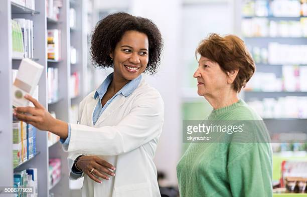 African American pharmacist assisting a customer in a pharmacy.
