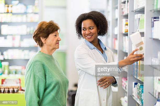 African American pharmacist assisting to a senior woman.