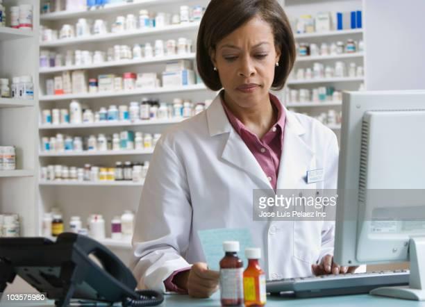 African American pharmacist filling prescription