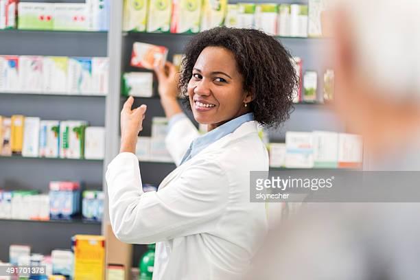 African American pharmacist serving customer in pharmacy.