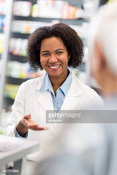 African American pharmacist talking to customer in pharmacy.