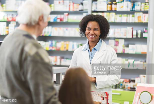 African American pharmacist talking to customers in a pharmacy.