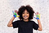 African American playful and creative kid getting hands dirty with many colors - in white brick background