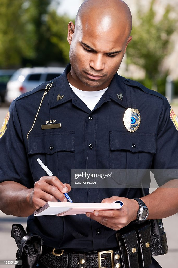 African American Police Officer Writing a Ticket : Stock Photo