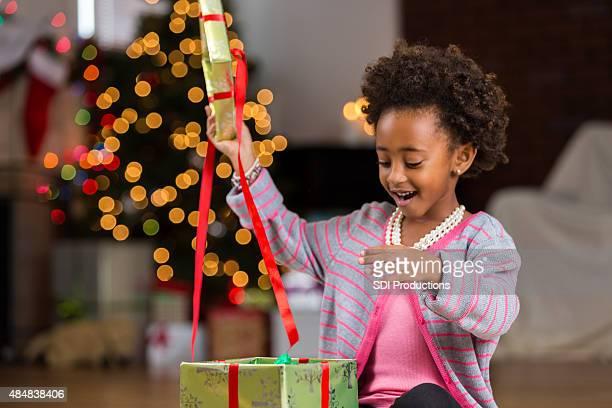 African American preschool girl opening Christmas present