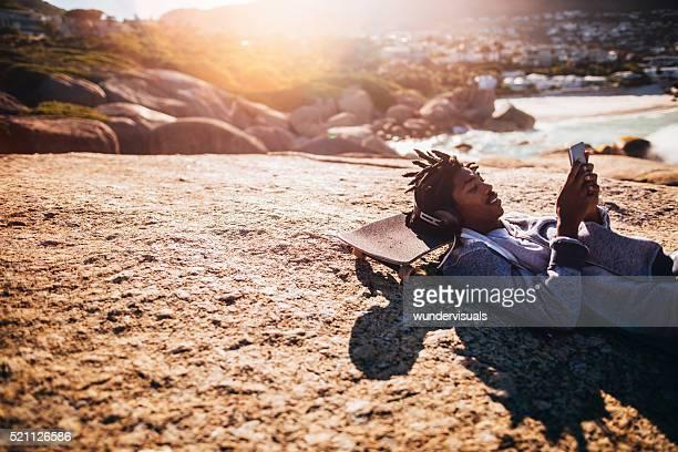 Afrikanische Amerikanische ausruhen und schaut an Smartphone am Strand