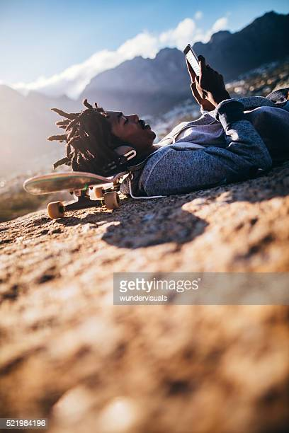 Afro-américain au repos et regardant Smartphone au bord de mer