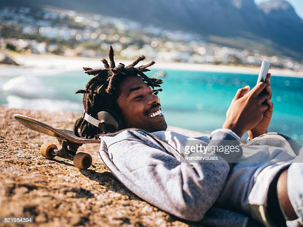African American Resting, Laughing and Looking at Smartphone at
