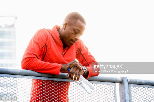 African American runner checking his watch on railing