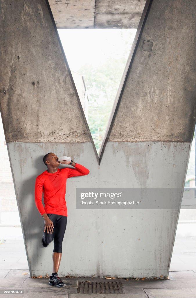 African American runner drinking water under overpass