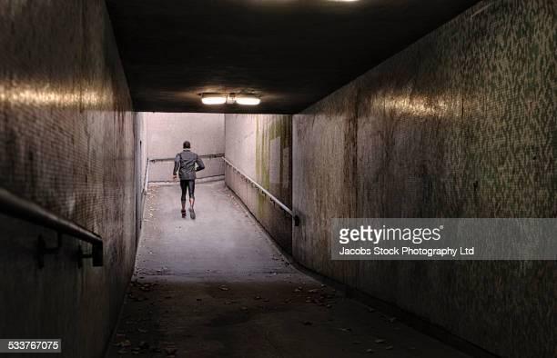 African American runner jogging in dilapidated underground hallway