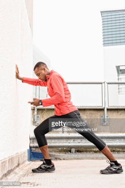 African American runner stretching against wall