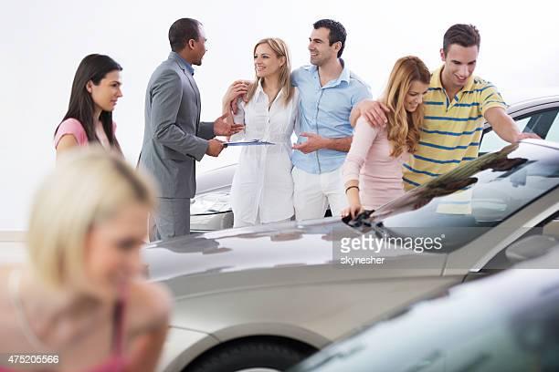 Vendedor-americano e os seus clientes em um Salão de Exposições.