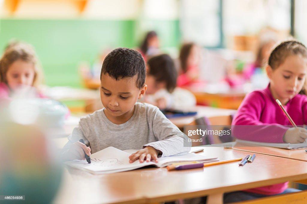 Écolier garçon afro-américain s'appuyant sur un cours à l'école. : Photo