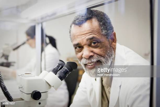 African American scientist using microscope in laboratory