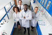 African American Scientist With Group Of Researchers In Modern Laboratory Happy Smiling, Mix Race Team Of Scientific Researchers In Lab Wearing White Coats And Protective Glasses