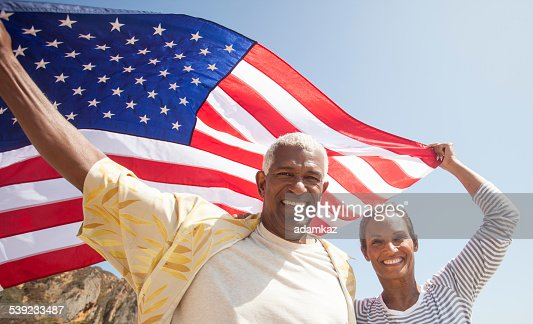 African American Senior Couple Carrying Usa Flag Stock
