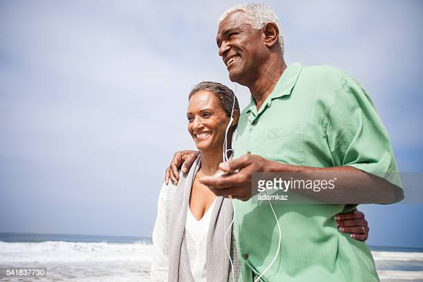 Couple de personnes âgées afro-américaine, écoutant de la musique ensemble sur la plage