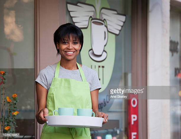 African American shopkeeper holding tray outside store