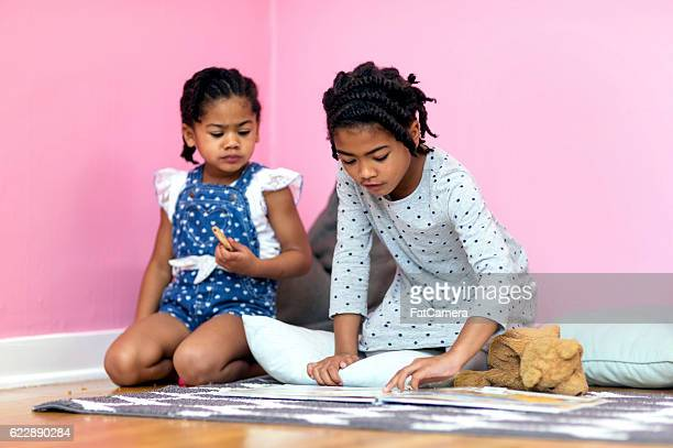 African American sisters reading a book and eating snacks