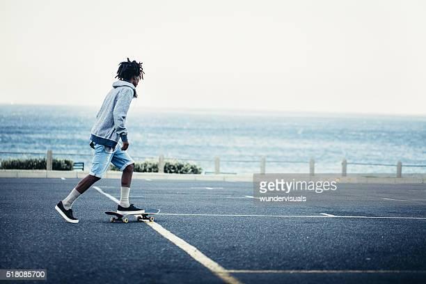 Afrikanische Amerikanische Skateboarden in am Meer gelegenen Parkplatz