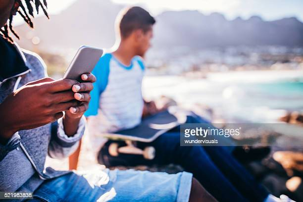 African American Skater Holding Smartphone at Seaside with backg