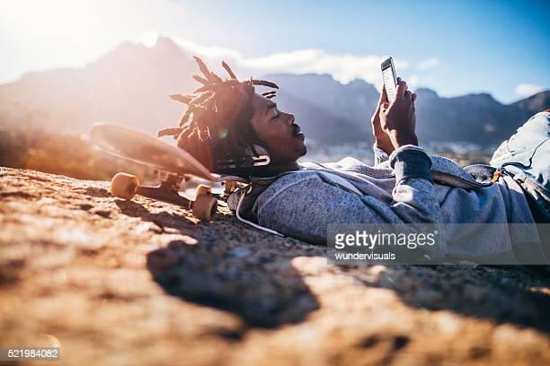 Afrikanische Amerikanische Schlittschuhläufer ausruhen und schaut an Smartphone am Meer