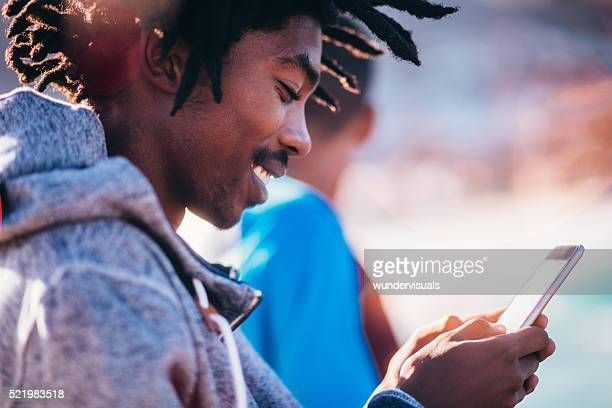 African American Skater Sitting and Looking at Smartphone Outsid