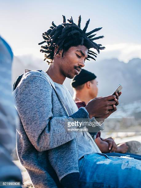 Afrikanische Amerikanische Schlittschuhläufer sitzen und schaut an Smartphone Ausserhalb