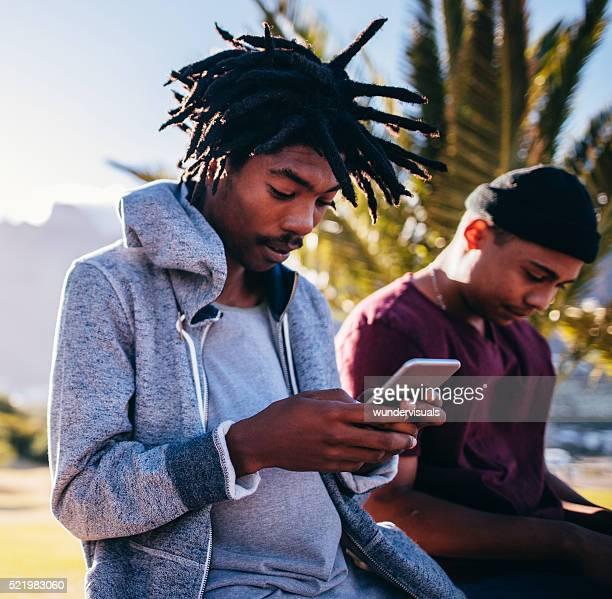 Afrikanische Amerikanische Schlittschuhläufer sitzen und schaut an Smartphone