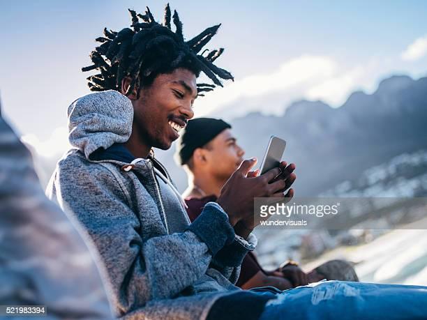 Afrikanische Amerikanische Schlittschuhläufer sitzen, lächeln und schaut an Smartpho
