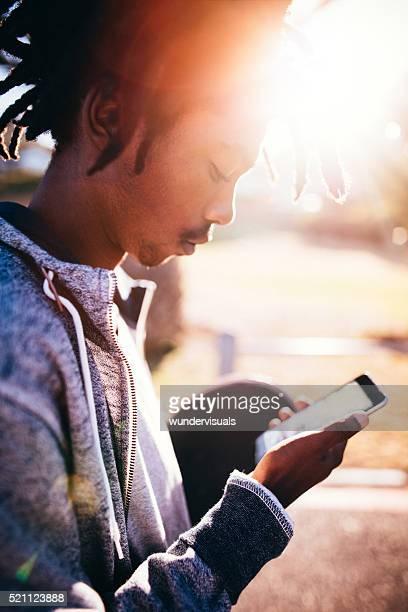 African Amerikanische Skater, steht und schaut an Smartphone