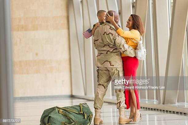 African American soldier greeting family in airport
