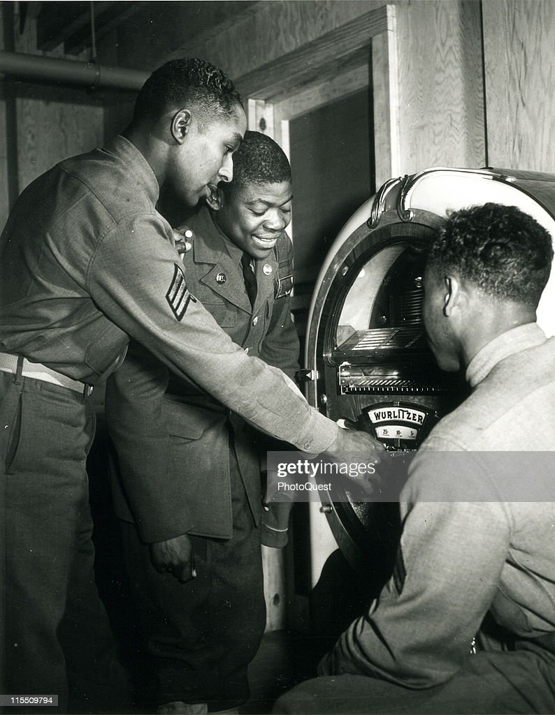 African American soldiers relax by listening to a jukebox during World War II, mid twentieth century.