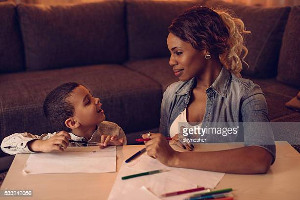 African American son sketching and talking to his mother.