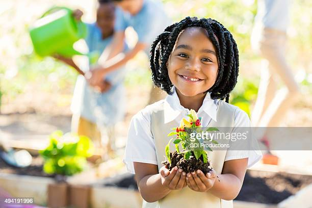 African American student holding plant while gardening during science class