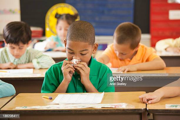 African American student wiping his nose at desk in classroom