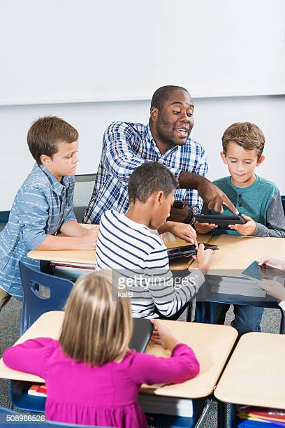 African American teacher and children, digital tablets