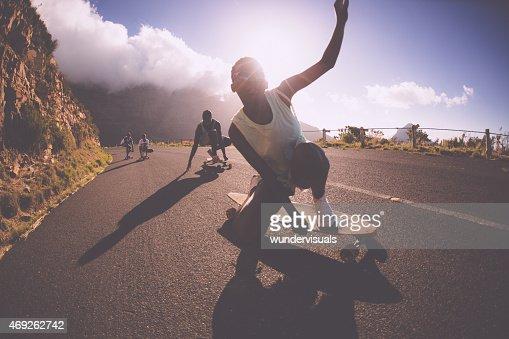 African American teen girl on a longboard doing downhill racing