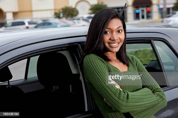 African American teenage girl leaning on car
