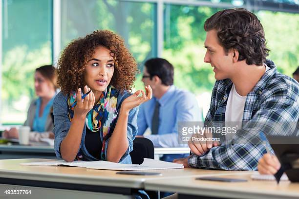 African American teenager explaining something to college classmate