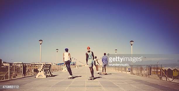 African American teenagers longboarding on a walkway at the beach