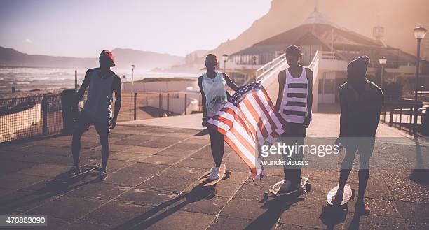 Americano africano adolescenti skateboard eseguendo una bandiera americana
