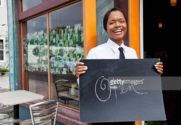 African American waitress outside restaurant open for business