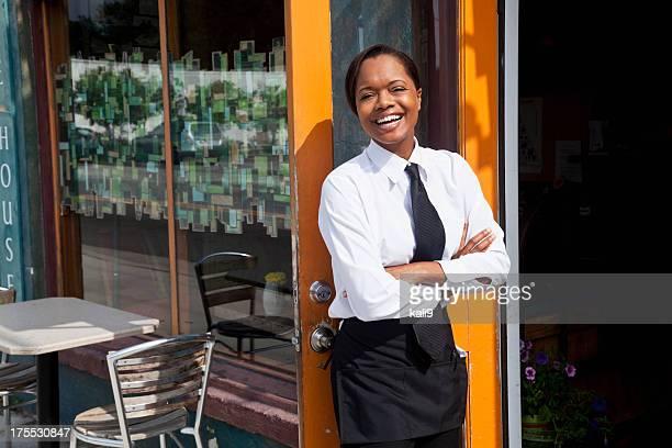 アフリカ系アメリカ人のウェイトレス立つ屋外レストラン