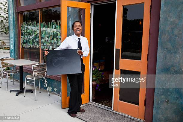 African American waitress standing outside restaurant with blank
