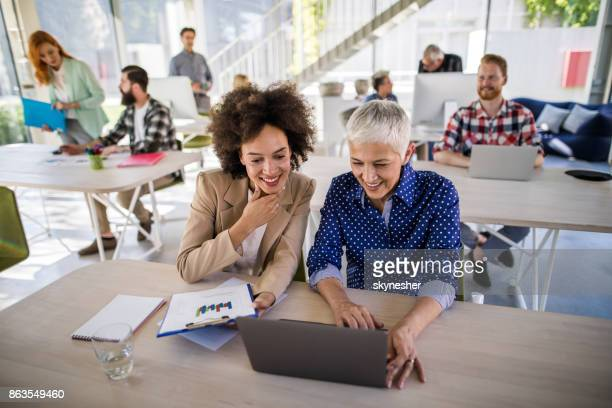 African American woman and her senior colleague working on laptop at corporate office.