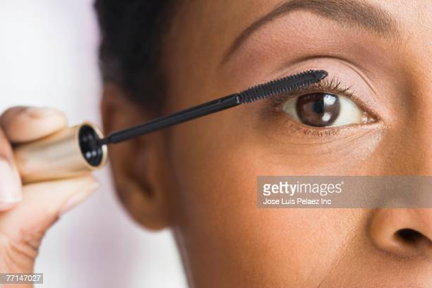 African American woman applying mascara