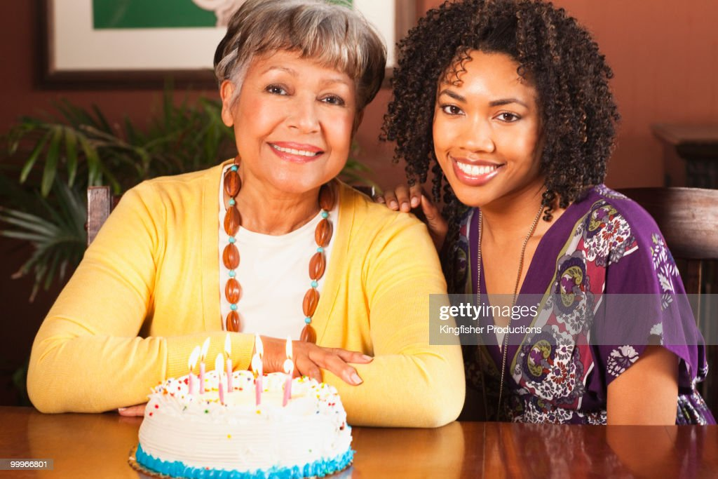 African American woman blowing out candles on birthday cake : Stock Photo