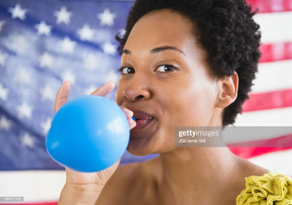 African American woman blowing up blue balloon